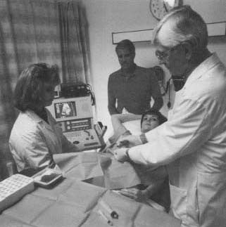 A doctor and nurse perform amniocentesis on a patient. The procedure is used to learn about the health of unborn babies.
