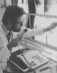 A doctor examines x-rays. By 1970 most Americans were receiving at least one X-ray exam every year from physicians and dentists.